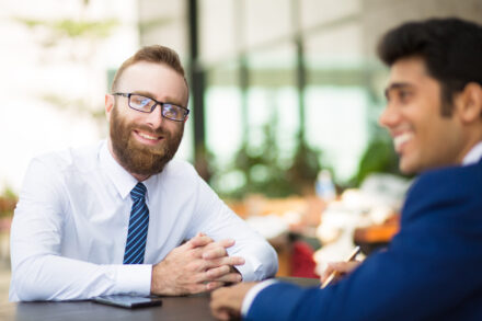 Smiling handsome bearded man meeting with business partner in cafe. Cheerful young businessman in glasses sitting at table and clenching hands while looking at camera. Successful businessman concept